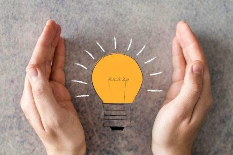 Two hands surrounding a lightbulb.